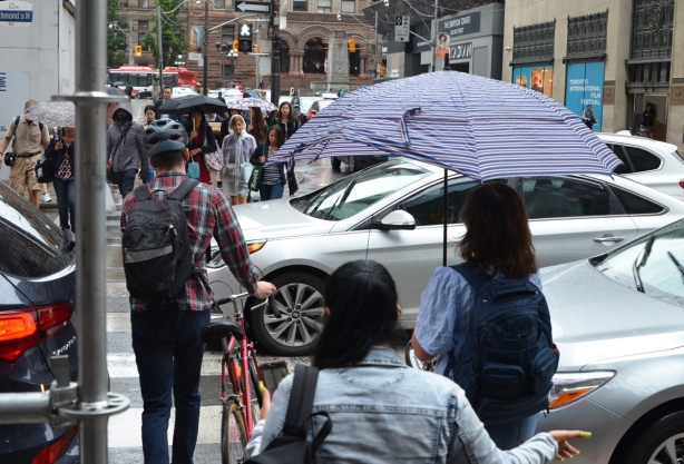 a man walks his bike across the street, between cars who are blocking traffic, also a woman with an umbrella gets ready to start across the street too