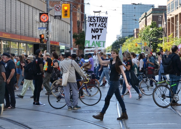 cyclists line Bay street at College street while they wait for a break in the climate strike march, one woman holds a sign that says destroy my ass not my planet