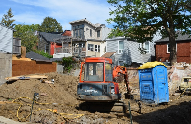 a digger and a blue porta-potty in a vacant lot construction site, with a row of backyards and backs of houses behind
