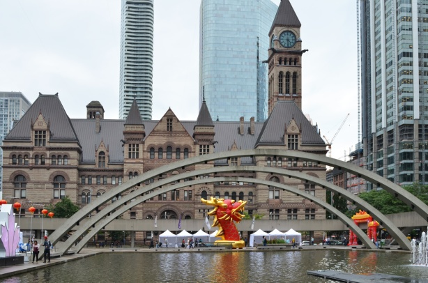 arches over the pool at Nathan Phillips square with old city hall behind, and a red and gold dragon head (very large) on display for dragon festival