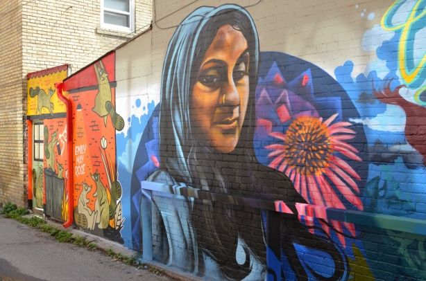 mural my drippin_soul of a woman in blue head scarf beside a large pinkish flower