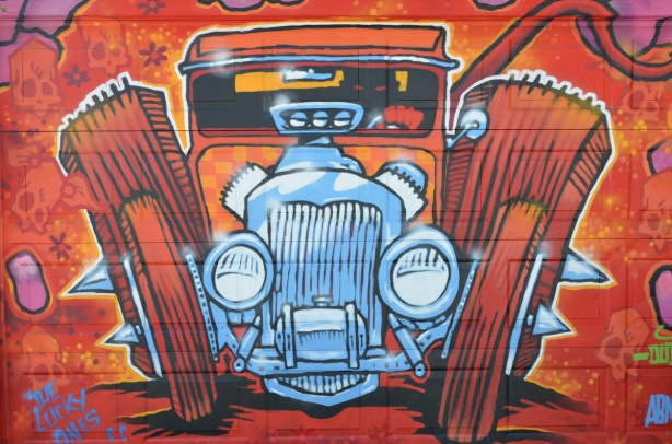 a fun mural of an old car by dudeman, in reds and oranges with front grille and radiator in blues