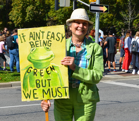 at the climate strike rally at Queens Park on a sunny morning in September, a middle age woman dressed all in light green, pants,jacket, and hat, and holding a sign with a picture of Kermit the frog that says It ain't easy being green but we must
