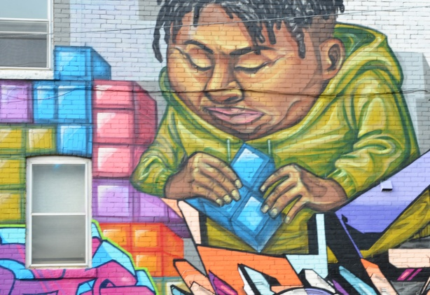 part of a mural by elicser of a couple putting tetris shapes together on a wall - heavy man in a long sleeved green hoodie
