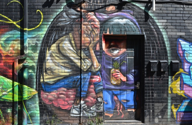 elicser mural on Croft street, man in doorway with a drink in a pineapple in his hand, other person sitting with hand over face