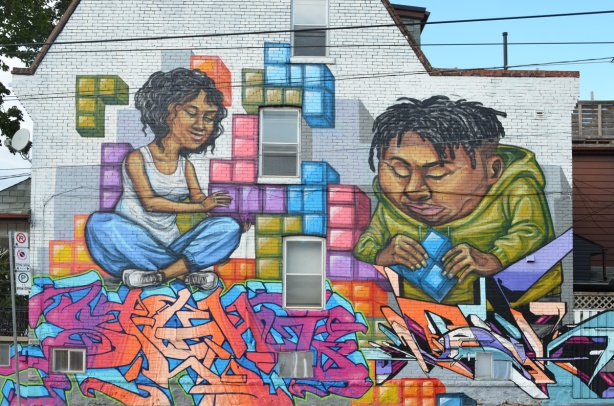 full mural on the side of a house, a mural by elicser of a couple putting tetris shapes together on a wall