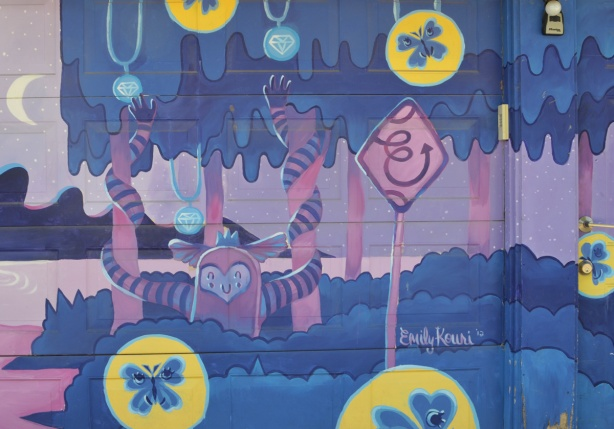 mural by emily kouri from 2012 on a garage door, in pinks and blues with yellow circles with butterflies in the circles