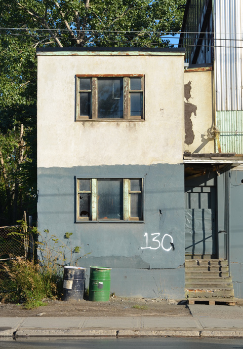 part of an empty and abandoned building, two storeys, old windows, the number 130 written in large white numbers