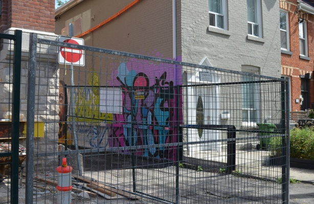 construction fence around a building being built, also a small beige house with white trim. Between the two is an entrance to an alley, there is a mural on the wall of the house, in the alley