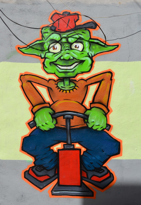 small green guy with big ears painted on a wall, orange shirt and blue pants. Hands on a trigger to start an explosion