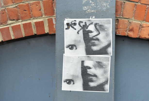 2 paper paste ups on a wall, both are the same, in grey tones, the lower part of a face with one eye beside it