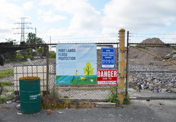 fence with signs, danger due to sign, plus sign that says Port Lands Flood Protection