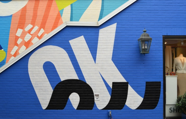 on the side of outdoor steps, a blue mural with the word OK in black and white such that it looks like the letters are curling up at the ends, 3 D effect