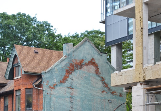 on the side of a brick house, two storey, Victorian, the remains of marks left behind on a house that was demolished, new development going up beside it