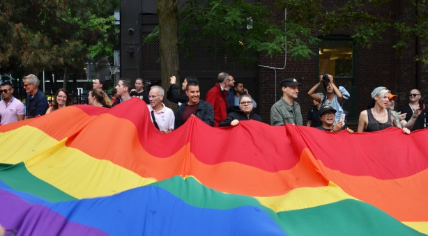 people holding the edge of a large pride rainbow flag