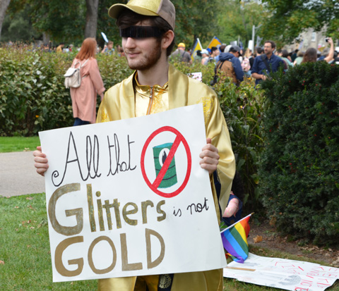 at the climate strike rally at Queens Park on a sunny morning in September, a young man dressed in gold and holding a sign that says All that glitters is not gold