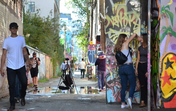 people in graffiti alley, walking, posing for photos, murals, art,