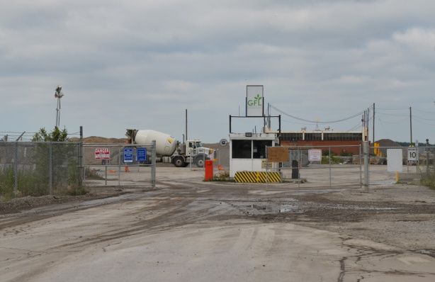 the last part of GFL (Green For life) structure to be torn down in the Port Lands, cement truck, dirt road, vacant land