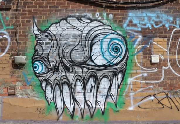 a large grominator graffiti on a brick wall, blue eyes