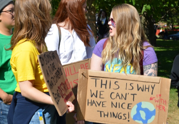 at the climate strike rally at Queens Park on a sunny morning in September, group of young people, including a woman with a cardboard sign that says This is why we can't have nice things