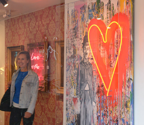 a woman in an art gallery, is standing by two pieces that use neon lights. One is large red heart as part of a painting with an image of Charlie Chaplin meant to look like a wall of graffiti, with a yellow neon light in a heart shape
