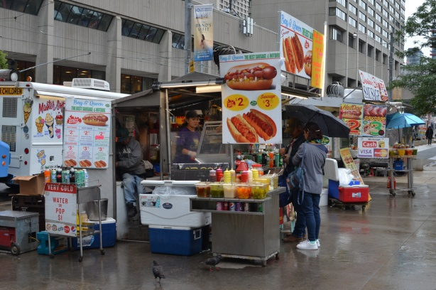 hot dog and sausage vendor on Queen street, woman under umbrella buying something, woman working inside the booth, a man sitting behind, many signs advertising their food