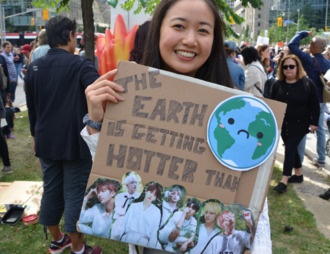 at the climate strike rally at Queens Park on a sunny morning in September, an Asian woman with a sign that says the earth is getting hotter than. At the bottom of the sign are pictures of a Korean boy band.