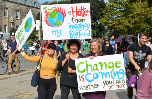 three people holding three placards, one says The earth is hotter than my imaginary boyfriend. also one says Change is coming whether you like it or not.