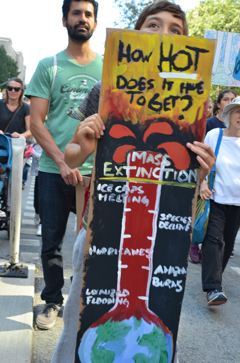 people at Toronto climate strike, walking along Wellesley street with signs, a giant thermometer with words how hot does it have to get, mass extinction is marked as the top temperature