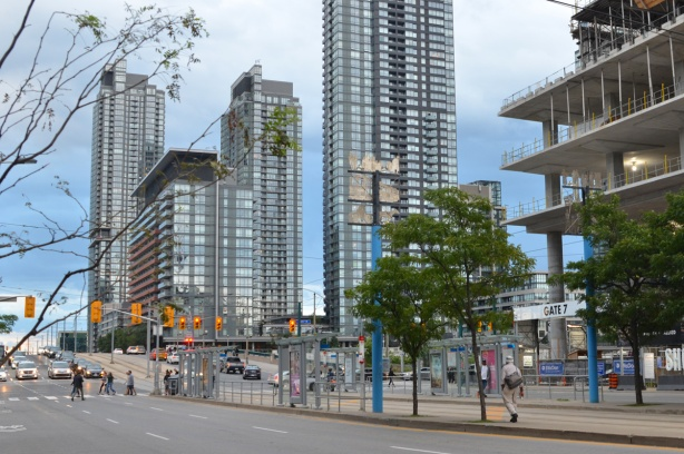 looking south on Spadina near Front, streetcar stop and shelters in the middle of Spadina, some people waiting for streetcars, 2 small trees, tall condos in the background