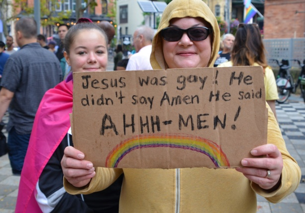 two women, one holding a sign that says Jesus was gay. He didn't say Amen, he said Ahhh men!