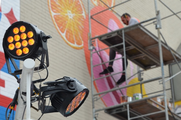 a man sits on scaffolding as he paints a mural, LED spotlights are in the foreground