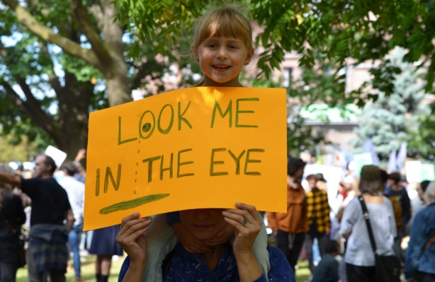 at the climate strike rally at Queens Park on a sunny morning in September, a girl is on her parent's shoulder. she is holding a yellow sign that says look me in the eye