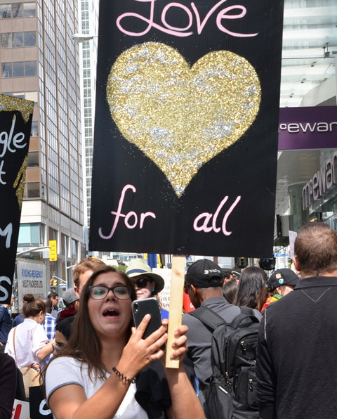 a young woman holds up a black sign with a large gold heart on it and the words love for all