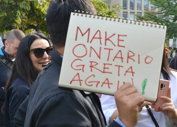 a man holds a spiral bound sketch book on which he's written Make Ontario Greta again.