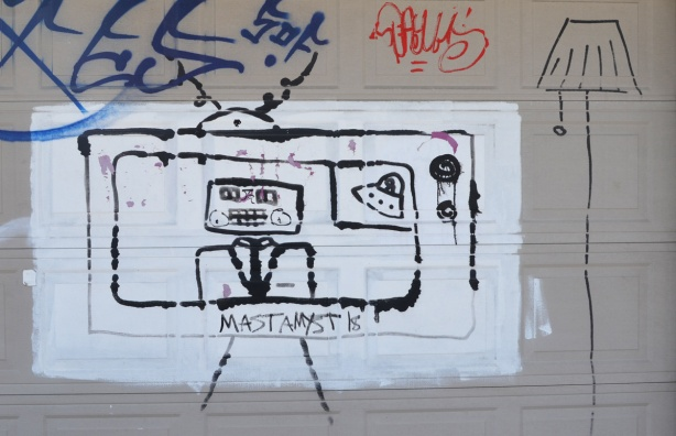 on a beige garage door, a white rectangle painted and on that, black drawing of a man with with a square head on TV, a lamp is beside the television