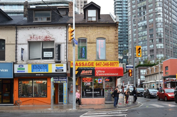 a shoe store, a massage parlour, and a convenience store, on the southwest corner of Yonge & wellesley, old brick buildings on Yonge with newer taller condos behind