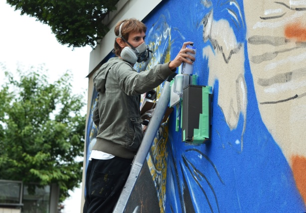 a man, street artist Mateo, spray paints a mural as he stands on a ladder. He's wearing a respirator, painting with blue paint