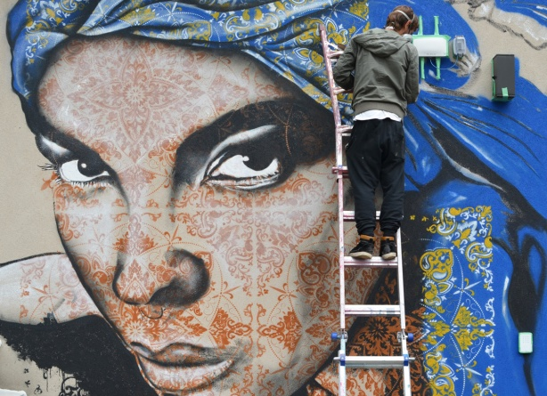 a man is on a ladder as he paints a mural of a woman with henna coloured stencils all over her face, and a blue and yellow head scarf,