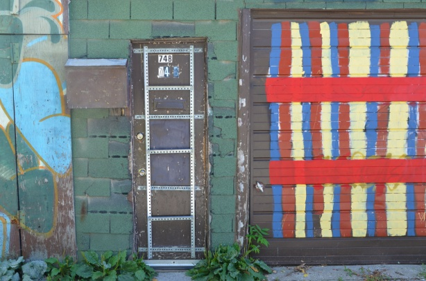 a narrow brown door with metal strapping grid on it beside a garage door with red, yellow, and blue stripes, wall is covered with green shingles