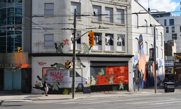 mural at the corner of Dundas and Victoria, is actually two murals in one. on the left is one by Emily May Rose, alley jams van and spray painting green raccoons. on the right is a tribute to Killy and Swagger rite, by one day creates