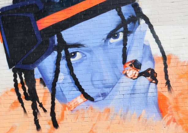 close up of part of mural, blue face, orange furry scarf, person wearing two rings, hat, dreadlocks,
