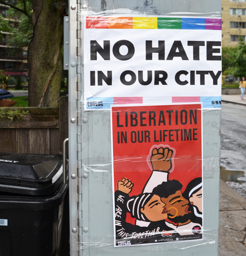 two posters on a metal box on the street, one says no hate in our city and the other says, liberation in our lifetime - the army of love