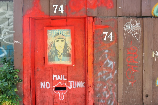 a wood wall and door in an alley painted red and brown, the number 74 on it twice, a mail slot with white paint around it to make slot look like mouth with tongue stuck out, no junk mail written too, a picture of a man on the door with the words we the future