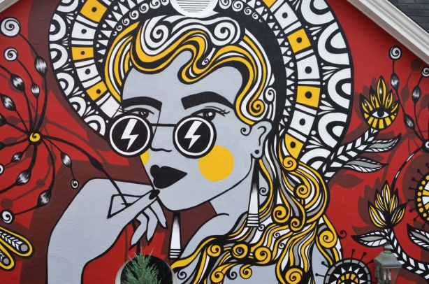 mural of a woman with long hair, stylized, in red, yellow and black and white