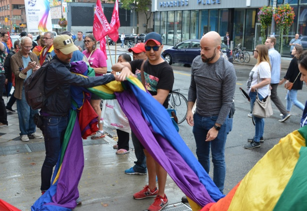 people helping to open up a giant pride rainbow flag