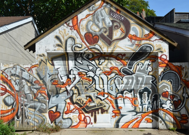 older mural on garage and fence on both sides, covers the whole thing, in oranges, browns, and greys,