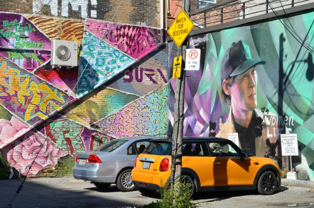 a bright orange mini cooper is parked with another car in a small parking lot with two murals, one by hello kirsten and a large portrait by janus
