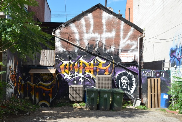 back of a building, in an alley, covered with street art. On top is a large white orek in white, green garbage bins in front
