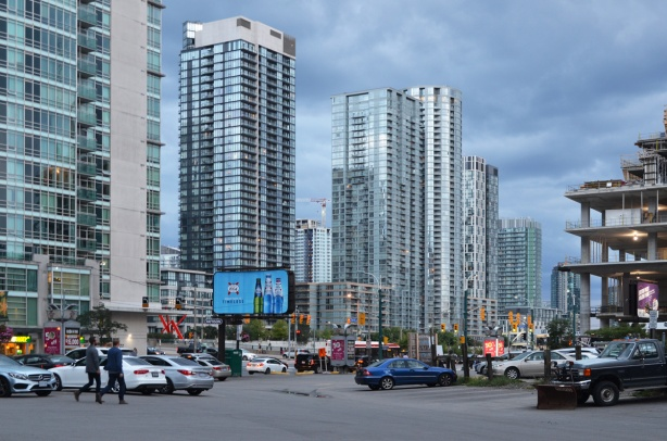 looking across parking lot at north east corner of Spadina and Front towards the traffic and lights at the intersection, billboard, people